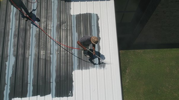two guys learning how to install a roof